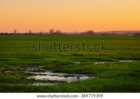 sunset over the rural landscape with field and village - stock photo