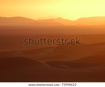 Sunset over the sand dunes of Erg Chebbi in the Sahara Desert near Merzouga, Morocco. - stock photo