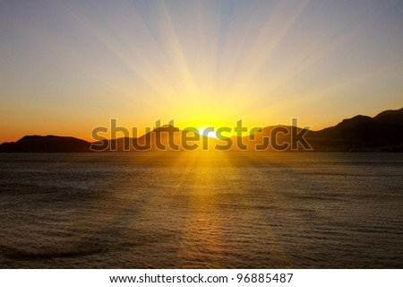 sunset over the sea against the rocks - stock photo