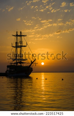 Sunset over the sea and a lone sailboat in the bay