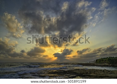 Sunset over the sea and stony coast