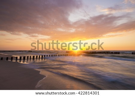 sunset over the sea, beach, beautiful sky and the waves breaking on the breakwater