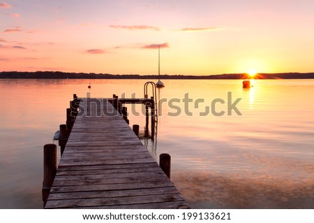 Sunset over the sea. Pier on the foreground - stock photo