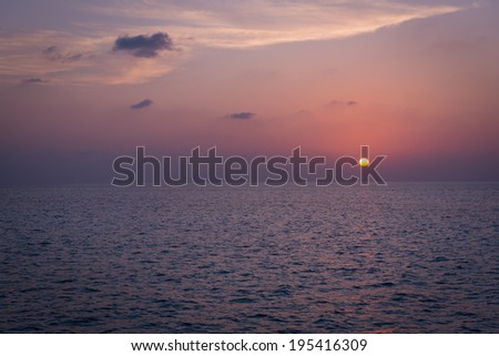 Sunset over the sea. Rays of the sun through the clouds. Setting sun painted the sky  in bright color. - stock photo