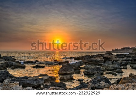 Sunset over the sea with stones on foreground - stock photo