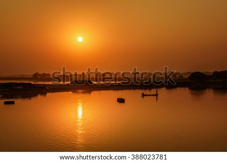 Sunset over the Taungthaman Lake with two fisherman silhouettes near Mandalay in Myanmar - stock photo