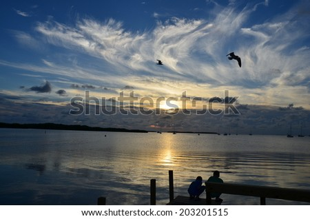 Sunset over the water in the Florida Keys, birds, people and clouds - stock photo
