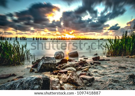 Sunset over the water with a view over the IJsselmeer and stormy cloudy skies. Sunbeams shine through the tombs. long shutter time photography with foggy water and dramatic atmosphere