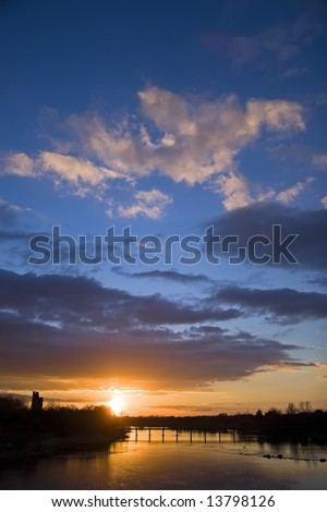 Sunset over the water with bridge and castle in background. - stock photo