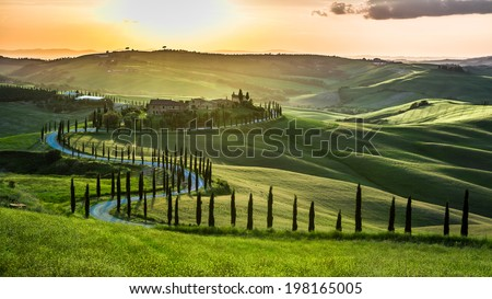 Sunset over the winding road with cypresses in Tuscany - stock photo