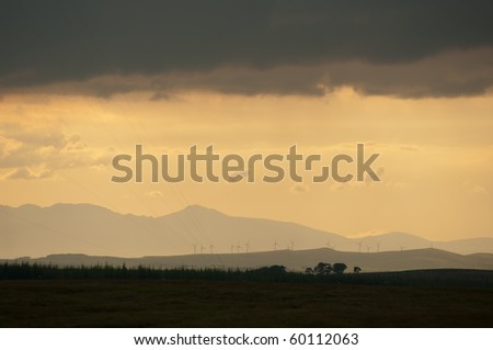 Sunset over turbines as clouds darken. Could be concept for weather uncertainty, worrying future or leaving environmental improvements too late. - stock photo