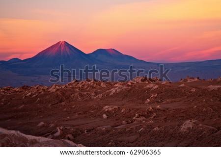 sunset over volcanoes Licancabur and Juriques and Valle de la Luna, Atacama desert, Chile - stock photo