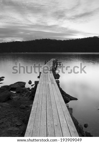 Sunset over water and jetty in black and white - stock photo