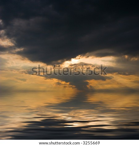 Sunset over water, with sunbeams trough heavy clouds. - stock photo