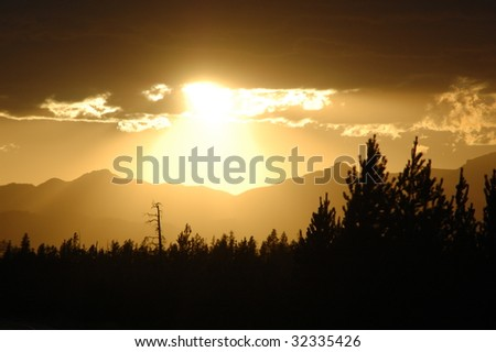 Sunset over Yellowstone with mountains, trees in silhouette - stock photo