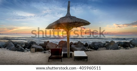 Sunset Panorama of a thatched  beach umbrella in Mauritius - stock photo