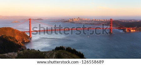Sunset Panoramic View of the Golden Gate Bridge from the Peak of Hawk Hill - stock photo