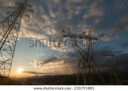 Sunset Pylons and Power lines - stock photo