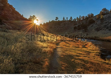 Sunset rays on a path beside a river, Sierra Nevada Mountains, California, USA. - stock photo