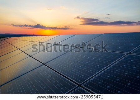 Sunset rays over a photovoltaic power plant - stock photo