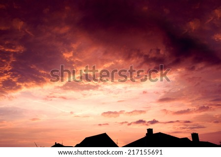 Sunset red sky with dark dramatic clouds over houses.