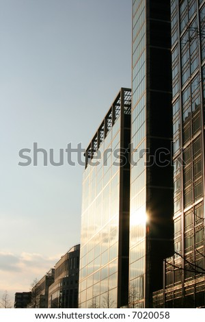Sunset reflecting on a glass corporate buildings - stock photo