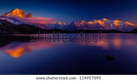 Sunset reflection in a lake in the Mont Blanc Mountains - stock photo