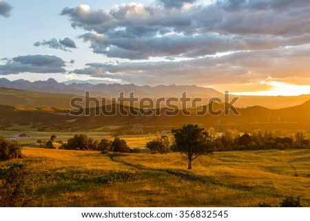 Sunset San Juans - Autumn sunset scene of a mountain valley at foot of the rugged Sneffels Range, part of San Juan Mountains, in Colorado Rockies. Mount Sneffels is the highest point in the range. - stock photo