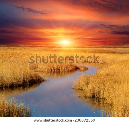 Sunset scene over small lake in steppe - stock photo