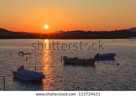 Sunset scene with nets and boat, Kanoni, Corfu, Greece - stock photo