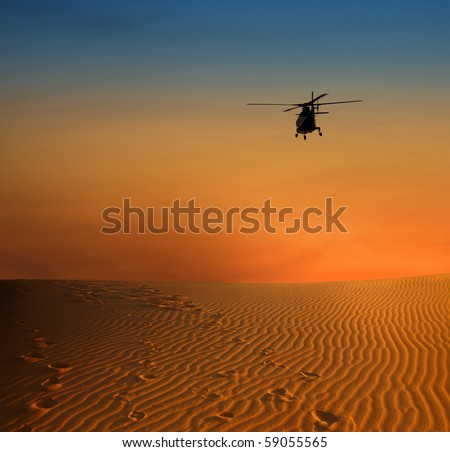 sunset scene with silhouette of a helicopter over desert - stock photo