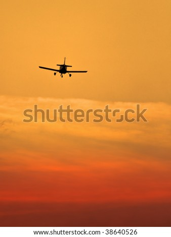 Sunset scene with silhouette of a landing plane
