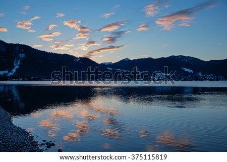 sunset scenery at lake tegernsee, illuminated clouds and water reflection - stock photo