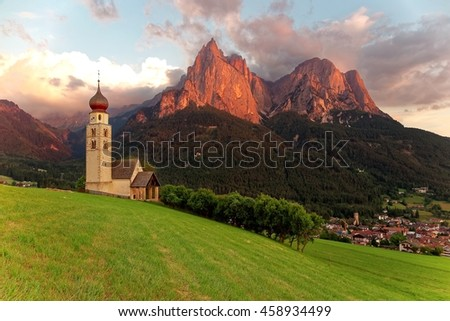 Sunset scenery of Church St. Valentin ( San Valentino ) on hillside, rugged peaks of Mountain Schlern with alpenglow in background & Village Seis am Schlern in the valley in South Tyrol, Italy, Europe - stock photo