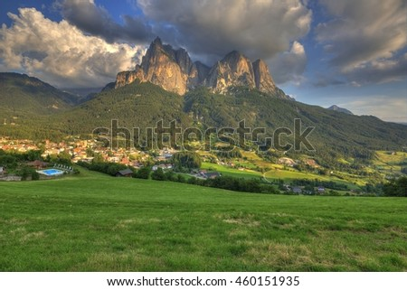 Sunset scenery of Dolomiti mountains under dramatic sky, with villages & green meadows at foothills of rugged Schlern (Sciliar) peaks in background, in Seis am Schlern, Castelrotto, South Tyrol, Italy - stock photo