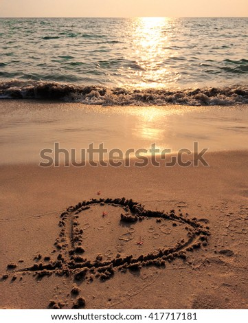 Sunset sea, heart on the beach and blue wave, heart on sand of beach, seaside activity, sand drawing, heart on beach, sunset on beach, summer vacation with love, romantic vacation, romantic beach view - stock photo