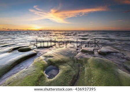 Sunset seascape with green moss foreground at Kudat Sabah. Slow shutter photograph. image contain soft focus and blur.