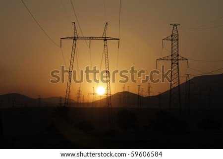 Sunset seen through a row of electricity pylons - stock photo