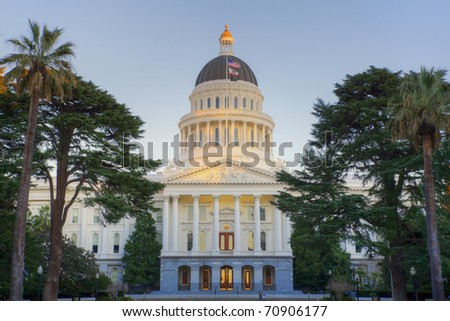 Sunset shines on top dome of California state capitol building in Sacramento