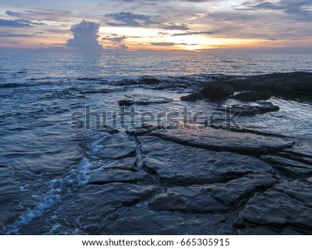 Sunset shot of the ocean waves rolling over rocks at Ko Kut island, east Thailand