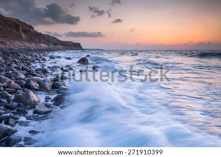 Sunset shots of a coastline of northern peninsula of Santorini island in Greece with the sun setting down the horizon - stock photo