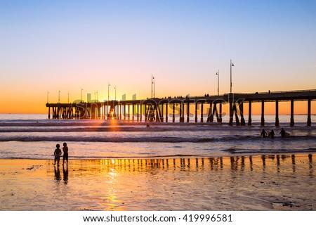 Sunset siblings // Venice Beach - stock photo