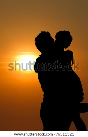 Sunset silhouette a young couple embracing