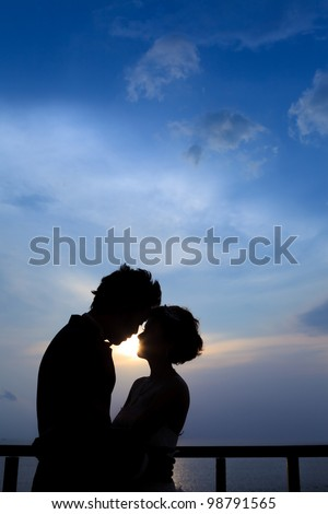 Sunset silhouette a young couple embracing - stock photo