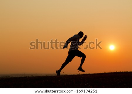 Sunset silhouette of a man sprinting uphill - stock photo