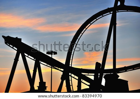 Sunset silhouette of a roller coaster in a theme amusement park - stock photo