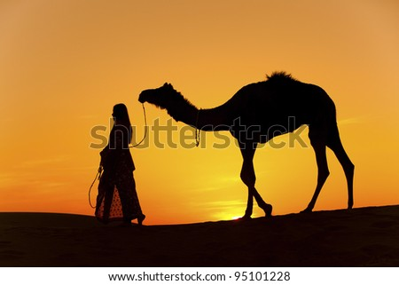 Sunset Silhouette of a women in a saree walking across the sand dunes of the Thar Desert with her camel. Rajasthan - India - stock photo