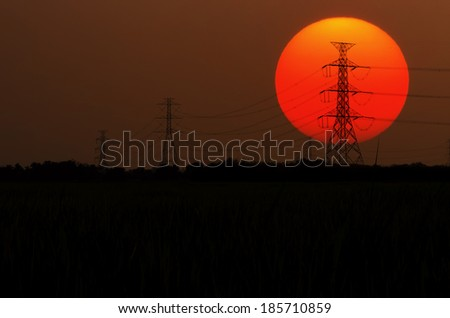 Sunset silhouette of electricity pole large sun. - stock photo