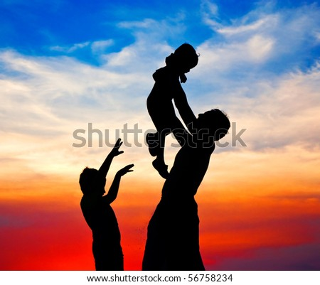 Sunset silhouette of family - stock photo