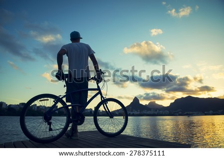 Sunset silhouette of man leaning against bicycle in front of scenic skyline view of Lagoa lagoon in Rio de Janeiro Brazil with Ipanema and Leblon on the horizon - stock photo